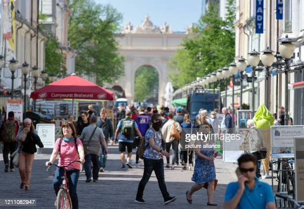 April 2020, Brandenburg, Potsdam: Some passers-by wearing face masks walk along the well-attended shopping mile Brandenburger Straße. Anyone who...