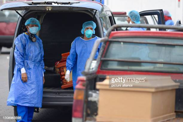 Men with protective suits load a coffin into a car in front of the hospital General del Guasmo The port city of Guayaquil is the most affected by...