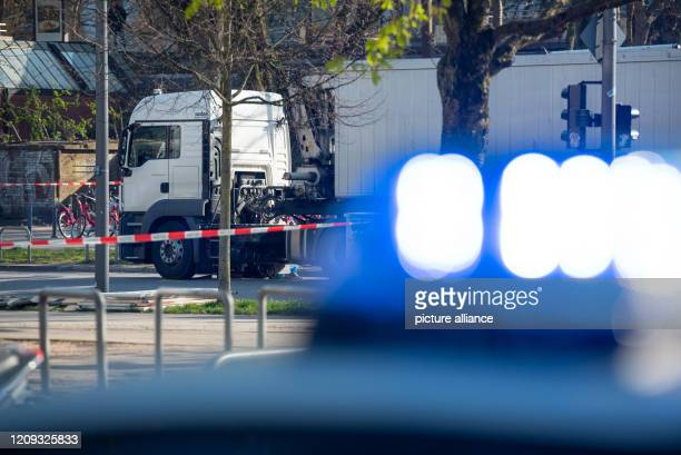 April 2020, Hamburg: The blue light of a patrol car shines in front of the truck standing at the cordoned-off accident site. A cyclist had been run...