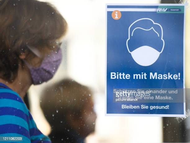 A woman with a face mask is sitting in a bus at the Konstabler Wache bus stop next to a poster with the words Bitte mit Maske Protect each other and...