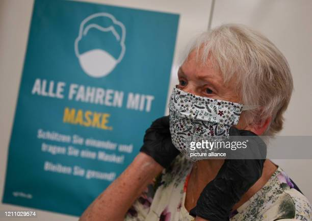 Christa Kögler from BergenEnkheim is standing in front of a poster with the inscription Alle fahren mit Maske Protect each other and wear a mask Stay...
