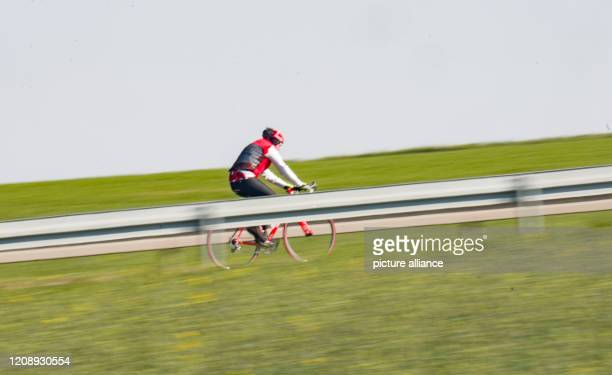 April 2020, Hessen, Karben: A man is riding his racing bike on a country road on the outskirts of the Hessian city . In times of the corona crisis,...