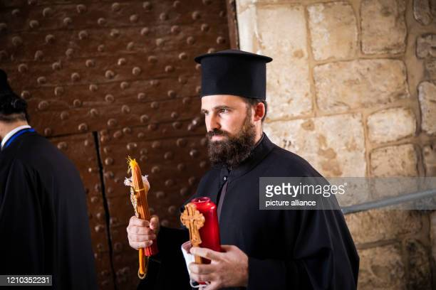 A Greek Orthodox priest takes part in the ceremony marking the Holy Fire celebrations during the coronavirus lockdown at the Old City According to...