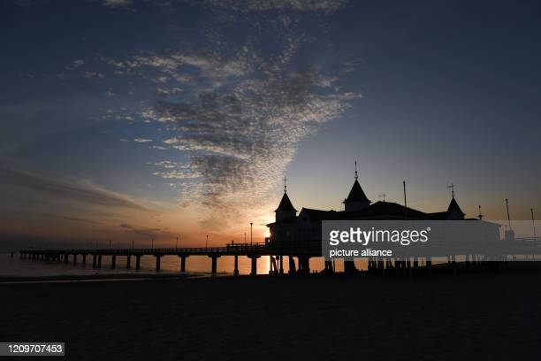 12 April 2020 MecklenburgWestern Pomerania Ahlbeck Clouds move in the early morning hours during sunrise in the sky above the pier on the island of...