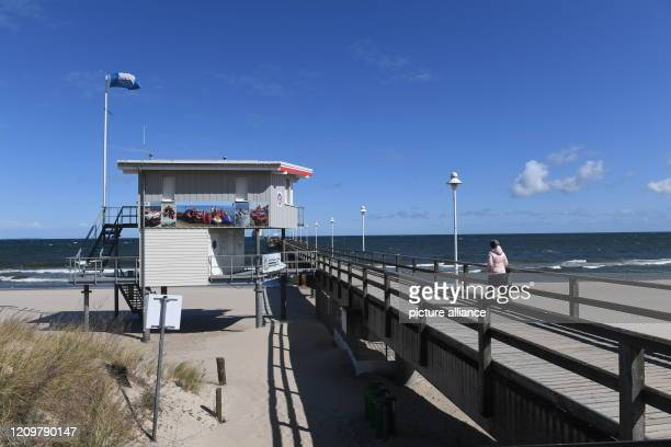 April 2020, Mecklenburg-Western Pomerania, Zinnowitz: One person walks on the pier on the Baltic beach on the island of Usedom . In order to slow...