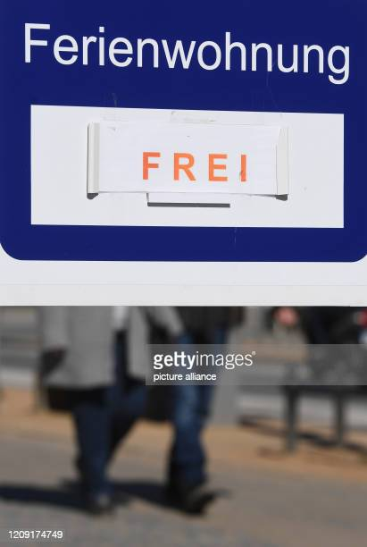 April 2020, Mecklenburg-Western Pomerania, Zinnowitz: Passers-by pass a sign for free holiday apartments. Due to the severe restrictions in public...