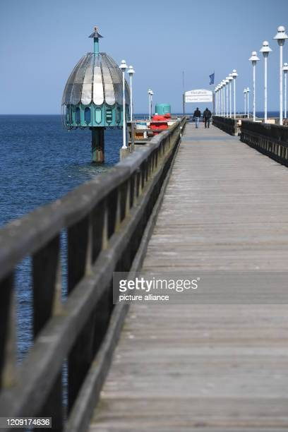 April 2020, Mecklenburg-Western Pomerania, Zinnowitz: Two walkers are walking on the pier in the Baltic resort of Zinnowitz on the island of Usedom....