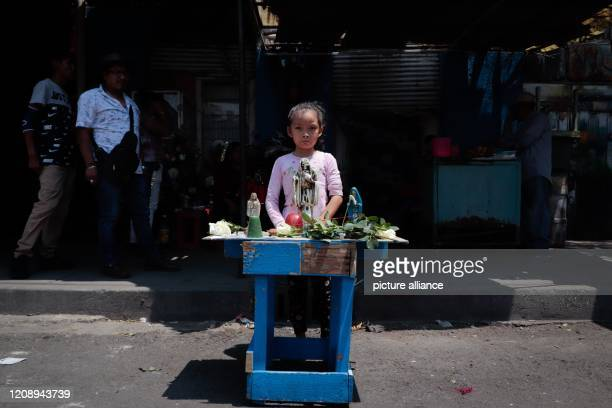 A girl stands behind an altar with roses an apple and a figure in honour of the Holy Death to ask him to protect her family Dozens of people gathered...