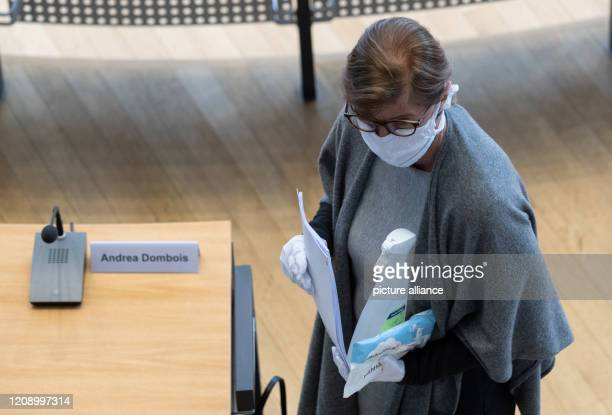Andrea Dombois first vice president of the Saxon state parliament wears a face mask and holds disinfectant in her hands before the start of a special...