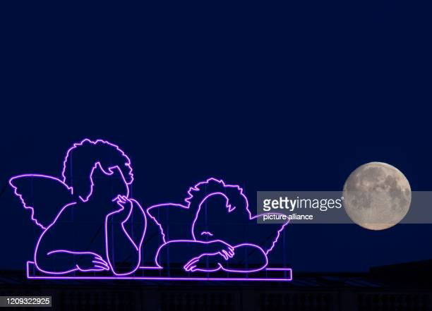 April 2020, Saxony, Dresden: The waxing moon sets in the morning next to the pink neon angels, modeled on the little angels on Raphael's Sistine...