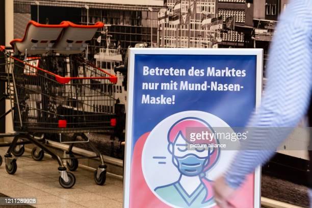 A sign with the inscription Entreten des Marktes nur mit MundNasenMaske is located at the entrance of a supermarket Since April 29 the obligation to...