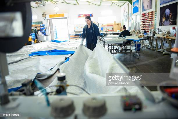 09 April 2020 SchleswigHolstein Lübeck An employee of the fabric processing company geodie Luftwerker holds a fabric panel in her hands for the...