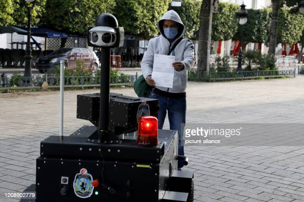 A citizen shows an exit permit to a Tunisian police robot which monitors the enforcement of the curfew aiming to curb the spread of the Coronavirus...