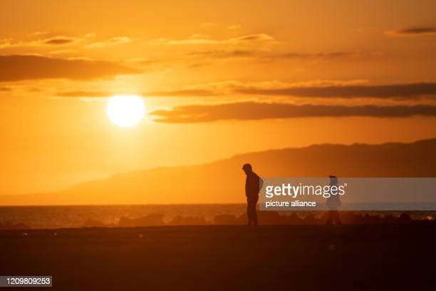 Two people are standing at the beach of Venice Beach watching the sunset Photo Maximilian Haupt/dpa
