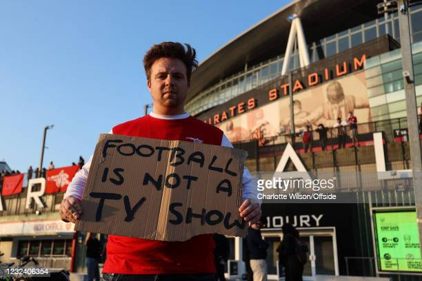 April 2021: A fan holds up a sign Reading Football is Not a TV Show outside The Emirates Stadium in protest of the proposed European Super League on...