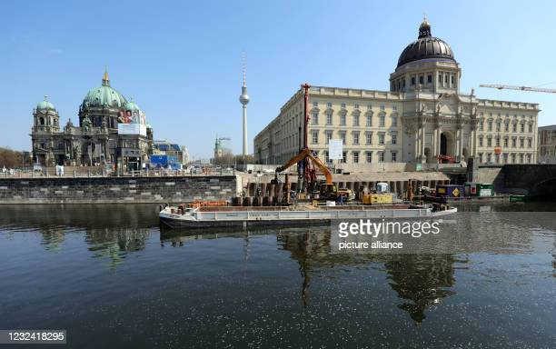 April 2021, Berlin: An excavator is deepening the bottom of the Spree at temperatures around 16 degrees Celsius and a bright blue sky. In the...