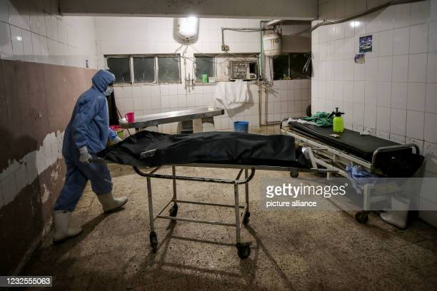 April 2021, Egypt, Cairo: Ahealth worker wearing full protective gear transfers a body of a person died of Covid-19 disease, inside the morgue of...