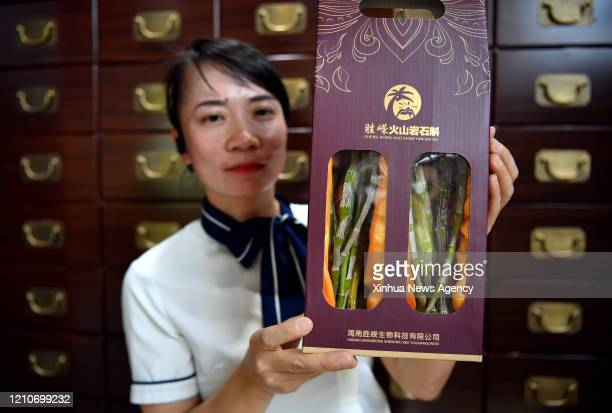 HAIKOU April 21 2020 A member of staff presents a dendrobium product in Shicha Village in Haikou south China's Hainan Province April 21 2020 Located...