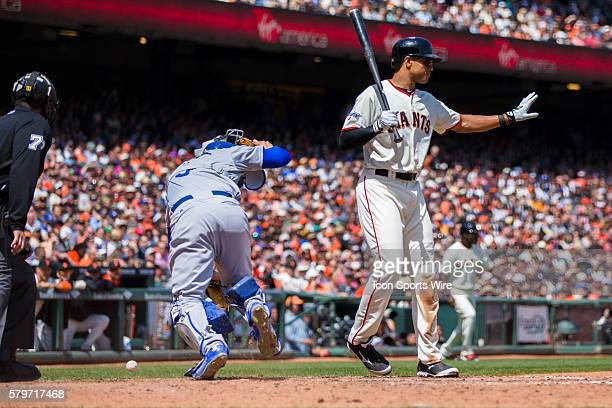 San Francisco Giants right fielder Justin Maxwell signals to hold as Los Angeles Dodgers catcher Yasmani Grandal chases the wild pouch during a Major...