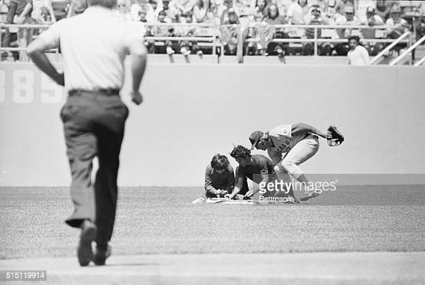 April 25 1976Los Angeles California On a dead run from centerfield Chicago Cubs Rick Monday reaches to rescue an American flag as two men attempt to...