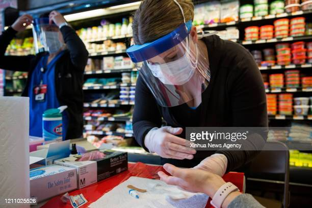 A healthcare worker takes a sample from a woman at a New York State Department of Health COVID19 antibody testing center at Steve's 9th Street Market...