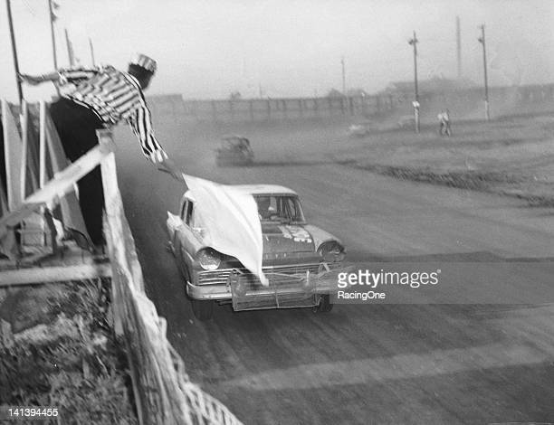 Race leader Paul Goldsmith takes the white flag during a NASCAR Cup race at the Greensboro Fairgrounds Goldsmith went on to victory in the race...