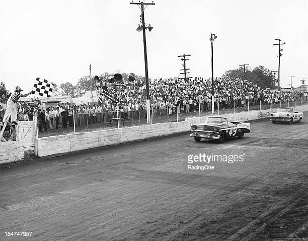 Bob Welborn takes the checkered flag to win the NASCAR Convertible Division race at Greensboro Fairgrounds over secondfinisher Gwyn Staley Both men...