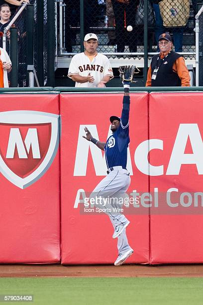 San Diego Padres center fielder Cameron Maybin reaches high to make the catch before the ball goes over the wall during the game between the San...