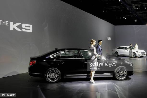April 3 2018Seoul South KoreaModels pose next to KIA Motor Company New Sedan Vehicle The K9 Unveil Event at Hotel's Grand Ballroom in Seoul South...