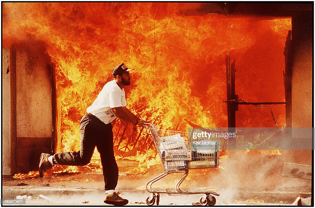 –– April 30, 1992–– The second day of the Riots on 3rd street I photographed this guy running past a burning Jon's market with a shopping cart full of diapers. I affectionately call this image 'A Huggies Run'.