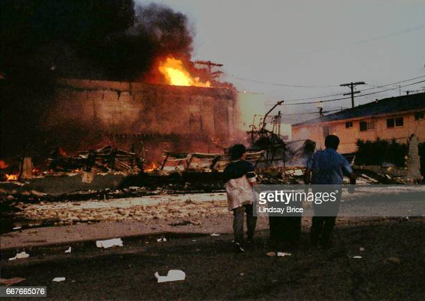 LOS ANGELES April 30 Rodney King Riot Two boys together carrying a garbage receptacle filled with water attempting to put out fires burning...