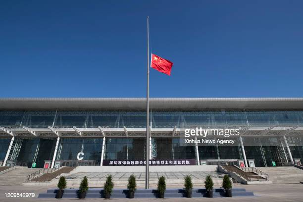 HARBIN April 4 2020 A Chinese national flag flies at halfmast to mourn for martyrs who died in the fight against the novel coronavirus disease...