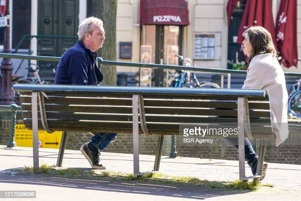 April 5: People keep their distance from each other sitting on a bench enjoying the sunny weather amid the coronavirus outbreak in Amsterdam,...