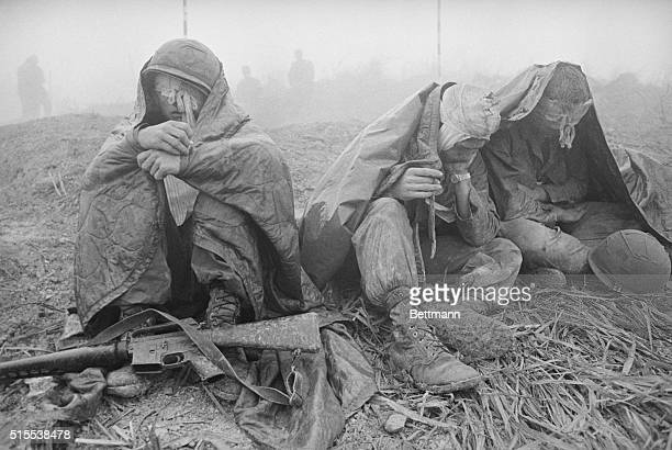 April 6 1968 Along Highway 9 South Vietnam Three wounded American fighting men huddle beneath their ponchos as they wait for medical evacuation...