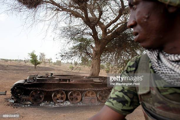 April 8- GWOZA, NIGERIA: A Nigerian soldier drives passed a destroyed military tank in Gwoza, Nigeria, the former base of Boko Haram, recently...