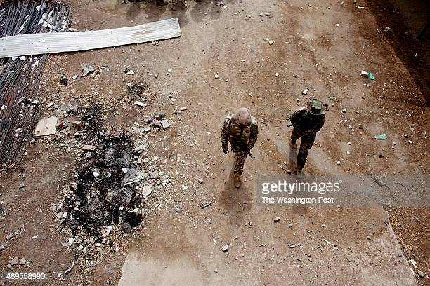 Nigerian soldiers walk toward the destroyed Emir's Palace in Gwoza Nigeria the former base of Boko Haram recently retaken by the Nigerian military