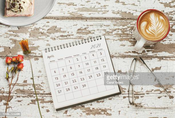 april calendar in feminine desktop with flowers, coffee cup, notebook, scissors - april stock pictures, royalty-free photos & images