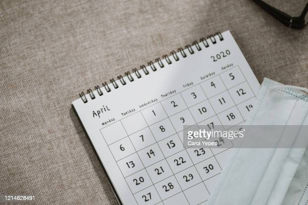 april calendar with protective mask.lockdown - 2020 stock pictures, royalty-free photos & images