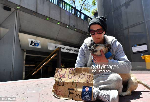 April Campbell and her dog Rocky wait for assistance from passersby in front of a train station in San Francisco California on Tuesday June 2016...