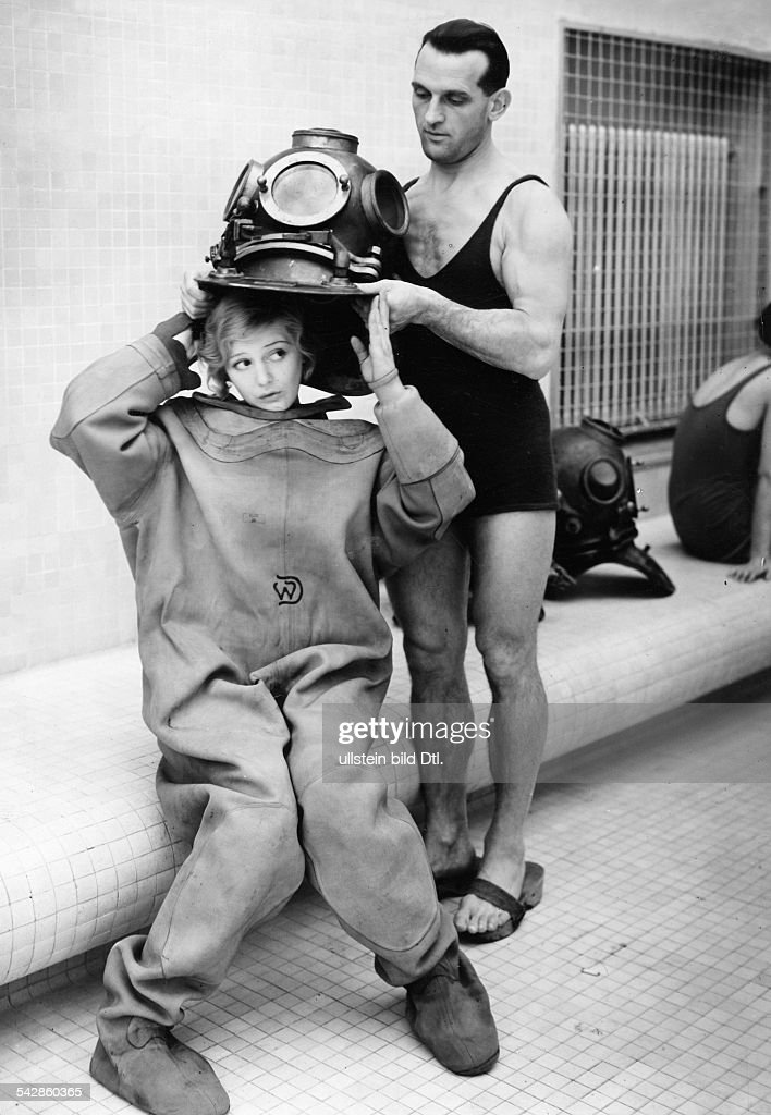 April fool hoax: Divers A diving instructor is helping a female diver to put on a diving helmet - 1933 - Vintage property of ullstein bild : News Photo
