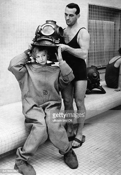 April fool hoax Divers A diving instructor is helping a female diver to put on a diving helmet 1933 Vintage property of ullstein bild