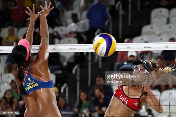 April Ross of United States spikes the ball as Fan Wang of China attempts to block during the Women's Beach Volleyball preliminary round Pool C match...