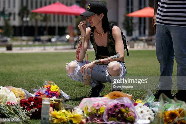 April Ross pauses after laying flowers at a makeshift memorial at Dr Phillips Center for the Performing Arts on June 13 2016 in Orlando Florida The...