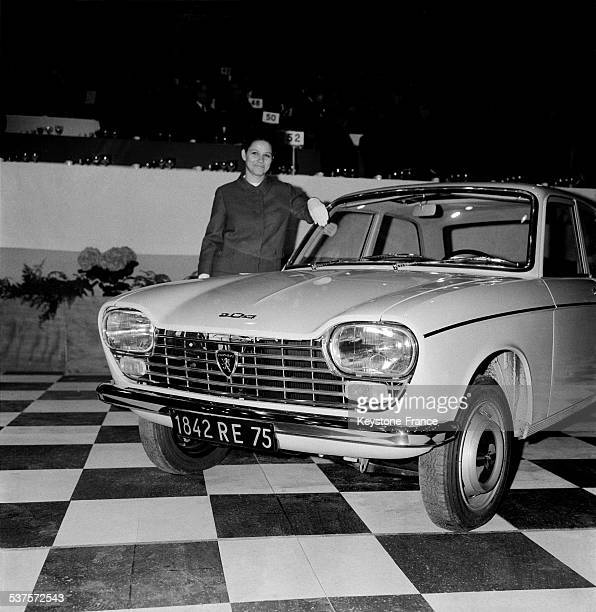 The Peugeot 204 Sedan 6 CV is presented by a model at the Sports Palace on April 23 1965 in Paris France