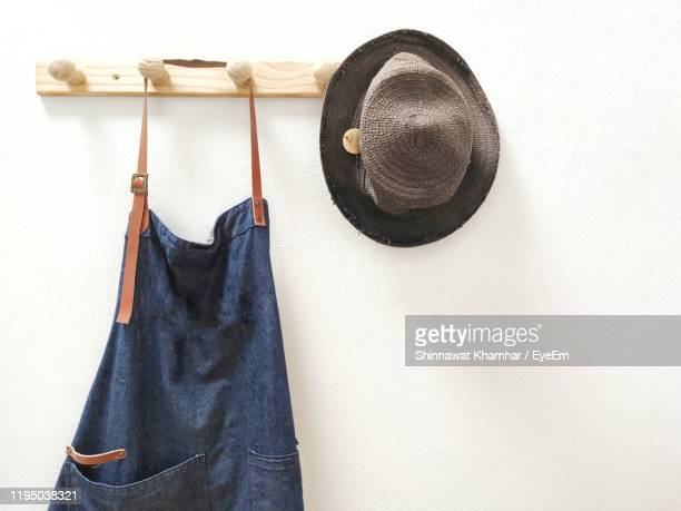 apron and hat hanging against white wall - apron stock pictures, royalty-free photos & images