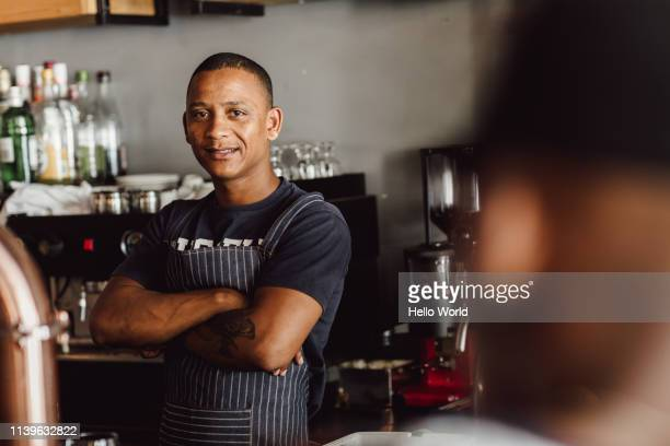 Apron wearing barman or chef looking ointo camera with folded arms and the out of focus head of customer in foreground