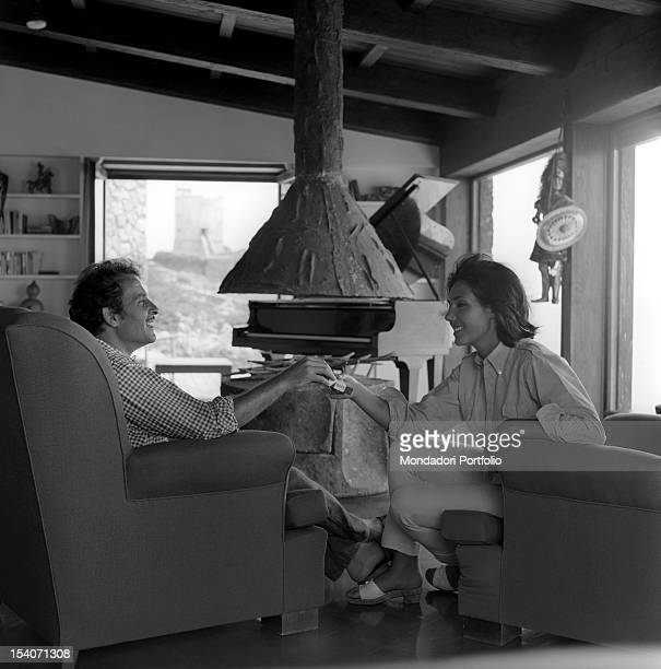 Apulian singer-songwriter Domenico Modugno, the most famous Italian artist all over the world, sits in an armachair; in front of him, his wife,...