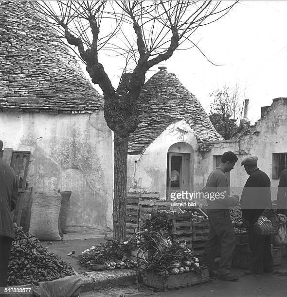 Männer auf dem Markt in Alberobello / Bari im Hintergrund ein Trullo ohne Jahr