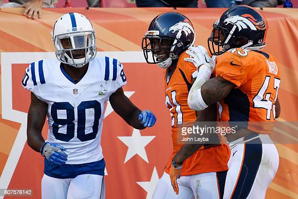 Aqib Talib of the Denver Broncos celebrates his picksix on a ball thrown by Andrew Luck of the Indianapolis Colts intended for Phillip Dorsett with...