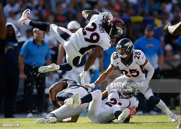 Aqib Talib of the Denver Broncos Chris Harris of the Denver Broncos and Bradley Roby of the Denver Broncos tackle Antonio Gates of the San Diego...
